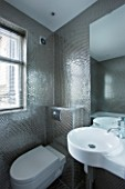 TANIA LAURIE  LONDON. STYLISH  CONTEMPORARY BATHROOM WITH WHITE SUITE AND SILVER HONEYCOMB EFFECT  MOSAIC TILES