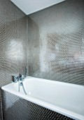 TANIA LAURIE  LONDON. STYLISH  CONTEMPORARY BATHROOM WITH WHITE BATH AND SILVER HONEYCOMB EFFECT MOSAIC TILES