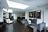 TANIA LAURIE  LONDON. INTERIOR OF LIVING / DINING AREA WITH LEATHER SOFAS  WHITE CHAIR AND ROOFLIGHT