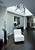 TANIA LAURIE  LONDON. INTERIOR OF LIVING AREA WITH GLASS ROOF (ROOFLIGHT) AND WHITE CHAIR WITH WOODEN FLOOR