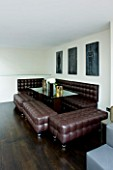 TANIA LAURIE  LONDON. INTERIOR OF DINING AREA WITH BROWN LEATHER SOFA AND STOOLS / BENCHES