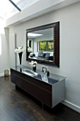 TANIA LAURIE  LONDON. INTERIOR OF LIVING AREA WITH CONTEMPORARY SIDEBOARD AND MIRROR