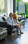 TANIA LAURIE  LONDON. TANIA LAURIE AND HER PARTNER DANIEL IN THEIR CONTEMPORARY LIVING ROOM LEADING OUT ONTO THE GARDEN DESIGNED BY CHARLOTTE ROWE