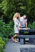 TANIA LAURIE  LONDON. TANIA LAURIE AND HER PARTNER DANIEL IN THEIR SMALL CONTEMPORARY GARDEN DESIGNED BY CHARLOTTE ROWE