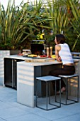 CONTEMPORARY FORMAL ROOF TERRACE/ GARDEN DESIGNED BY DATA NATURE ASSOCIATES: GIRL SITTING AT A TABLE BESIDE THE BARBEQUE