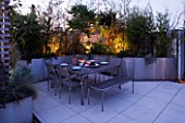 CONTEMPORARY FORMAL ROOF TERRACE/ GARDEN DESIGNED BY DATA NATURE ASSOCIATES: SEATING AREA AT NIGHT WITH LIGHTING. TABLE  CHAIRS  TRELLIS AND RAISED BEDS