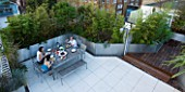 CONTEMPORARY FORMAL ROOF TERRACE/ GARDEN DESIGNED BY DATA NATURE ASSOCIATES: VIEW DOWN ONTO GARDEN WITH SEATING AND DINING AREA. PEOPLE EATING EVENING MEAL AT LARGE TABLE.