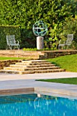 DAVID HARBER SUNDIALS: ARMILLARY SPHERE SUNDIAL AND SWIMMING POOL WITH STONE STEPS AND METAL CHAIRS