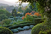 PROVENCE  FRANCE: GARDEN OF NICOLE DE VESIAN  LA LOUVE: CLIPPED TOPIARY AND RHUS TYPHINA (STAGS HORN SUMACH)  AND COUNTRYSIDE (GARRIGUE) BEYOND