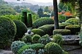 PROVENCE  FRANCE: GARDEN OF NICOLE DE VESIAN  LA LOUVE: CLIPPED TOPIARY SHAPES   RHUS TYPHINA (STAGS HORN SUMACH)  AND COUNTRYSIDE (GARRIGUE) BEYOND