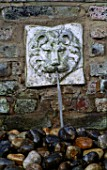 WATER FEATURE: WALL MOUNTED LIONS HEAD WATER SPOUT ABOVE STONE SINK FILLED WITH PEBBLES.  DESIGNER: ANTHONY NOEL