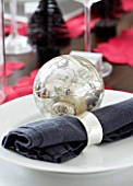 CHRISTMAS TABLE SETTING - NAPKIN AND SILVER BAUBLE ON A PLATE. SARAH EASTEL LOCATIONS/ DI ABLEWHITE
