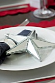 CHRISTMAS TABLE SETTING - NAPKIN AND SILVER MIRRORED STAR DECORATION ON A WHITE PLATE. SARAH EASTEL LOCATIONS/ DI ABLEWHITE