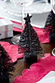 CHRISTMAS TABLE SETTING -MINIATURE BLACK CHRISTMAS TREE DECORATION ON A WHITE PLATE. SARAH EASTEL LOCATIONS/ DI ABLEWHITE