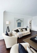 CHRISTMAS - LIVING ROOM WITH TRIPOD LAMP  CREAM SOFAS  CUSHIONS AND WALL PRINT. SARAH EASTEL LOCATIONS/ DI ABLEWHITE