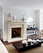 CHRISTMAS - LIVING ROOM WITH CREAM FIREPLACE  CREAM SOFA  WOODEN COFFEE TABLE  SILVER GLOBES  MIRROR. SARAH EASTEL LOCATIONS/ DI ABLEWHITE