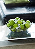 CHRISTMAS - METAL DISH WITH APPLES AND SILVER BAUBLES ON GLASS COFFEE TABLE IN LOUNGE. SARAH EASTEL LOCATIONS/ DI ABLEWHITE