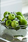 CHRISTMAS - SILVER MATAL DISH WITH GREEN APPLES AND SILVER BAUBLES ON A GLASS COFFEE TABLE. SARAH EASTEL LOCATIONS/ DI ABLEWHITE