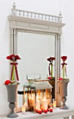 CHRISTMAS - TABLE ON LANDING WITH URNS  RED AMARYLLIS AND RED BAUBLES  MIRROR  STORM LANTERN  CANDLES.  SARAH EASTEL LOCATIONS/ DI ABLEWHITE