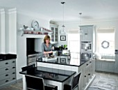 CHRISTMAS - DI ABLEWHITE MAKING TEA IN HER BLACK AND WHITE KITCHEN. SARAH EASTEL LOCATIONS/ DI ABLEWHITE
