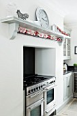 CHRISTMAS -DETAIL OF BLACK COOKER AND WHITE WALLS IN THE KITCHEN. SARAH EASTEL LOCATIONS/ DI ABLEWHITE