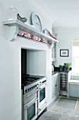 CHRISTMAS -DETAIL OF BLACK COOKER AND WHITE WALLS IN THE KITCHEN  CLOCK ON WALL. SARAH EASTEL LOCATIONS/ DI ABLEWHITE