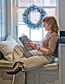 CHRISTMAS - DI ABLEWHITE READING IN THE WINDOW SEAT IN THE KITCHEN. SARAH EASTEL LOCATIONS/ DI ABLEWHITE
