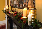 CLARE MATTHEWS CHRISTMAS HOUSE INTERIOR: THE DINING ROOM - CANDLES  BAUBLES  HOLLY AND TAPESTRY ABOVE THE FIREPLACE