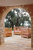 DESIGNER GINA PRICE - CORFU - VILLA ONEIRO - VIEW THROUGH ARCHWAY TO OUTDOOR PATIO WITH WOODEN SEATS AND CUSHIONS BESIDE THE VILLA