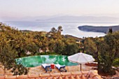 DESIGNER GINA PRICE - CORFU - VILLA ONEIRO -  VIEW FROM BEDROOM BALCONY TO THE INFINITY POOL WITH MOROCCAN SUN LOUNGERS AND SEA AND ALBANIAN MOUNTAINS BEYOND