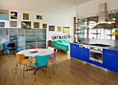 ROSE GRAY AND SCULPTOR DAVID MACILWAINE: DAVIDS ART STUDIO WITH COLOURED CHAIRS  BLUE KITCHEN UNITS  AND CANVASES ON WALLS