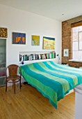 ROSE GRAY AND SCULPTOR DAVID MACILWAINE: DAVIDS ART STUDIO WITH CANVASES ON WALL BESIDE BED WITH BLUE AND GREEN BEDSPREAD