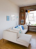 ROSE GRAY AND SCULPTOR DAVID MACILWAINE: DAVIDS ART STUDIO WITH CANVASES ON WALL BESIDE SOFA WITH BLUE  GREEN AND WHITE CUSHIONS  EASEL AND MOBILE