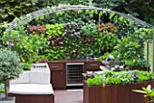 CHELSEA FLOWER SHOW 2009: FRESHLY PREPPED GARDEN BY ARALIA. OUTDOOR KITCHEN/ENTERTAINING AREA WITH EDIBLE LIVING WALL PLANTED WITH BABY SALAD LEAVES
