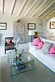 DESIGNER: CLAIRE SKINNER  ROU ESTATE  CORFU: HOUSE 11 (LAVENDULA) INTERIOR - LIVING ROOM IN GREY  CREAM AND PINK. GLASS COFFEE TABLE  SOFA WITH CUSHIONS  IRIS IN VASE