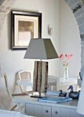 DESIGNER: CLAIRE SKINNER  ROU ESTATE  CORFU: HOUSE 11 (LAVENDULA) INTERIOR - LIVING ROOM IN GREY  CREAM AND PINK. CENTRANTHUS IN VASE  ARCH AND LAMP