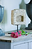 DESIGNER: CLAIRE SKINNER  ROU ESTATE  CORFU: HOUSE 11 (LAVENDULA) INTERIOR - LIVING ROOM IN GREY  CREAM AND PINK. WOODEN GREY CABINET WITH LAMPS  SCULPTURE AND CENTRANTHUS