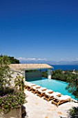 PRIVATE VILLA  CORFU  GREECE. DESIGN BY ALITHEA JOHNS - DECKCHAIRS BESIDE THE SWIMMING POOL WITH VIEW OF ALBANIA BEYOND
