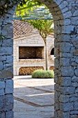 PRIVATE VILLA  CORFU  GREECE. DESIGN BY ALITHEA JOHNS - VIEW THROUGH ARCHWAY TO WOOD STORE