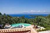 VILLA ONEIRO  CORFU  DESIGNER GINA PRICE: VIEW ACROSS THE SWIMMING POOL WITH SUN LOUNGERS FROM MOROCCO AND VIEW TO ALBANIA