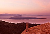 THE ROU ESTATE  CORFU: DAWN VIEW OVER ROOFTOP TO SEA AND ALBANIAN MOUNTAINS