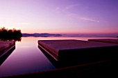 THE ROU ESTATE  CORFU: THE SWIMMING POOL AT DAWN WITH THE ALBANIAN MOUNTAINS BEHIND