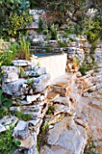 THE ROU ESTATE  CORFU: THE SWIMMING POOL AREA - ROCK FACE BESIDE THE PLUNGE POOL
