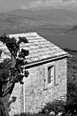 THE ROU ESTATE  CORFU: BLACK AND WHITE IMAGE OF HOUSE WITH ALBANIA IN BACKGROUND