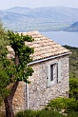 THE ROU ESTATE  CORFU: STONE BUILDING WITH ALBANIAN MOUNTAINS IN THE BACKGROUND