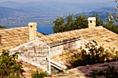 THE ROU ESTATE  CORFU: TILED ROOFS WITH SEA AND ALBANIA BEYOND