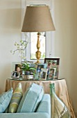 THE KAPARELLI ESTATE  CORFU - CIRCULAR TABLE WITH LAMP AND FRAMED PHOTOGRAPHS
