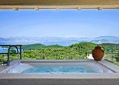 THE KAPARELLI ESTATE  CORFU - UNDERCOVER JACUZZI/HOT TUB ON RAISED PATIO WITH VIEW OUT TO SEA WITH ALBANIAN MOUNTAINS BEYOND