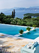 THE KAPARELLI ESTATE  CORFU - PATIO/SEATING AREA WITH VIEW OVER SWIMMING POOL OUT TO SEA WITH ALBANIAN MOUNTAINS BEYOND