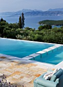 THE KAPARELLI ESTATE  CORFU - VIEW OVER PATIO AND SWIMMING POOL OUT TO SEA WITH ALBANIAN MOUNTAINS BEYOND